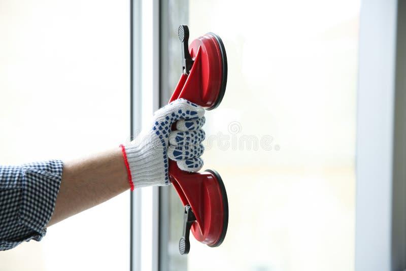 Muratore che per mezzo del sollevatore di aspirazione durante l'installazione della finestra all'interno immagini stock libere da diritti