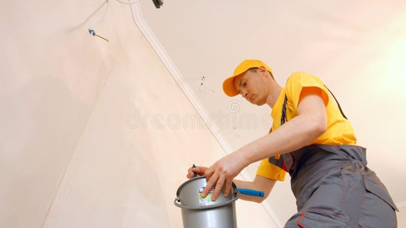 Muratore che prepara parete per wallpapering immagine stock