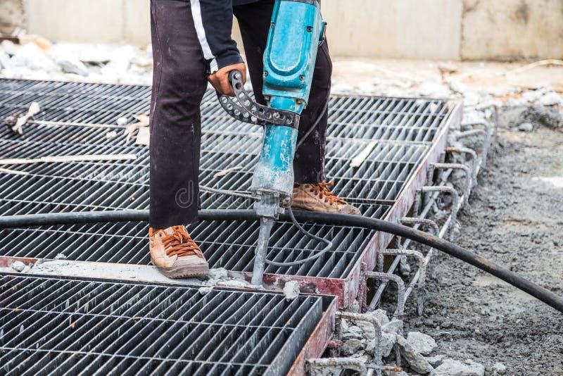 Muratore che usando il cemento del pavimento del trapano del martello pneumatico fotografia stock