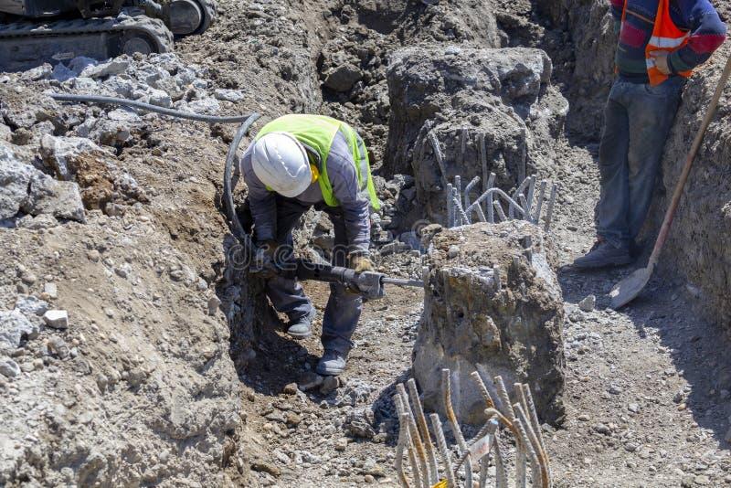 Muratore con le colonne di cemento armato della rottura del martello pneumatico fotografia stock libera da diritti