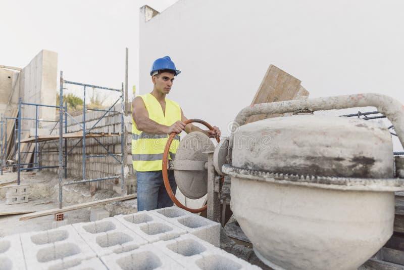 Muratore di Youn che regola betoniera in posto di lavoro b immagini stock libere da diritti