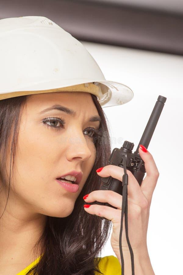 Muratore femminile serio che parla con un walkie-talkie immagini stock