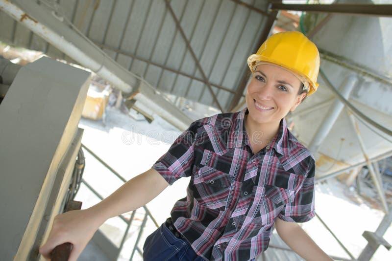 Muratore femminile sorridente del ritratto del primo piano al sito fotografia stock libera da diritti