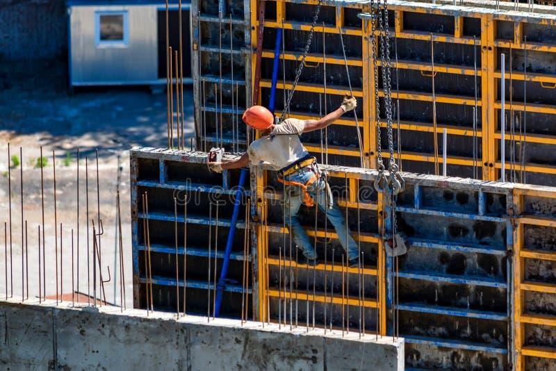 Muratore nel casco di sicurezza al cantiere di edificio residenziale fotografia stock