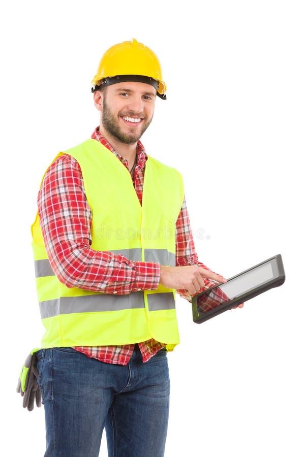 Muratore sorridente che per mezzo di una compressa digitale antiurto fotografia stock