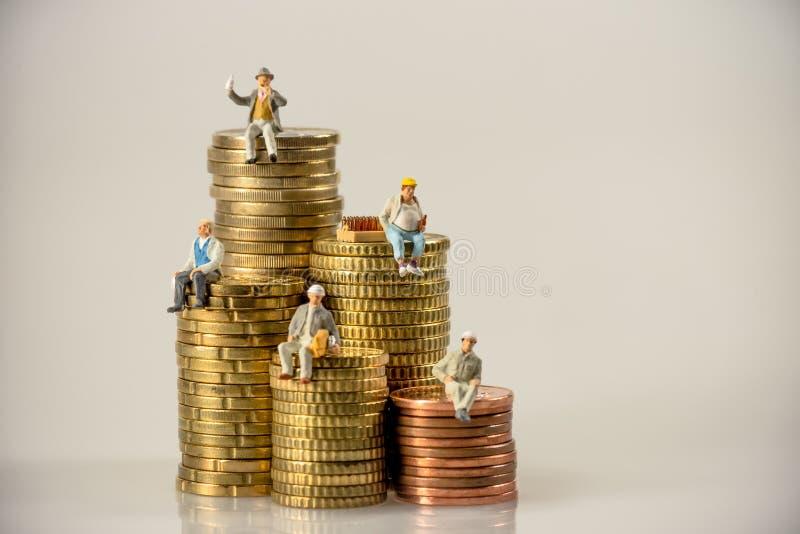 Muratori che si siedono sui mucchi della moneta dei soldi fotografie stock