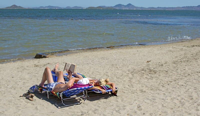 Murcia, España - 22 de junio de 2019: Pares felices que leen un libro y que se relajan en la playa durante un día de verano solea fotos de archivo