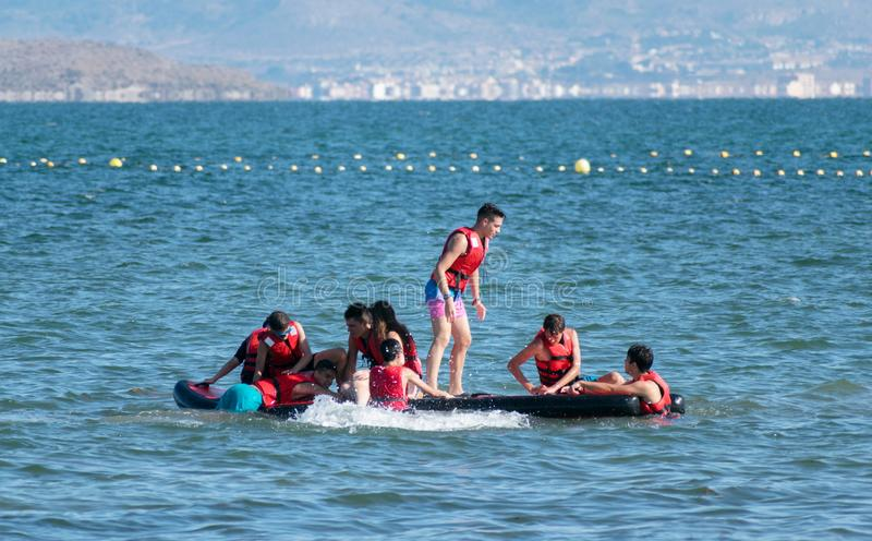Murcia, Spain, July 17, 2019: Happy children playing on the beach at the day time. Concept of summer vacation and friendly family active adventure board boy stock photos