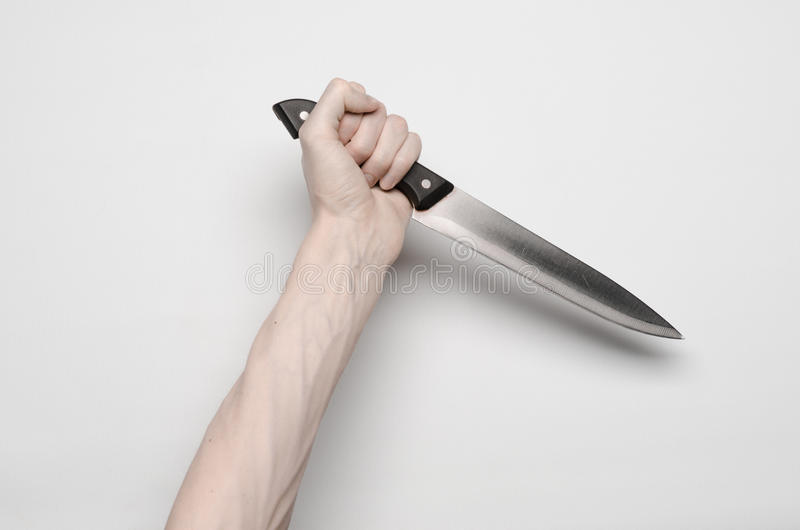 Murder and Halloween theme: A man's hand reaching for a knife, a human hand holding a knife isolated on a gray background in stock photography