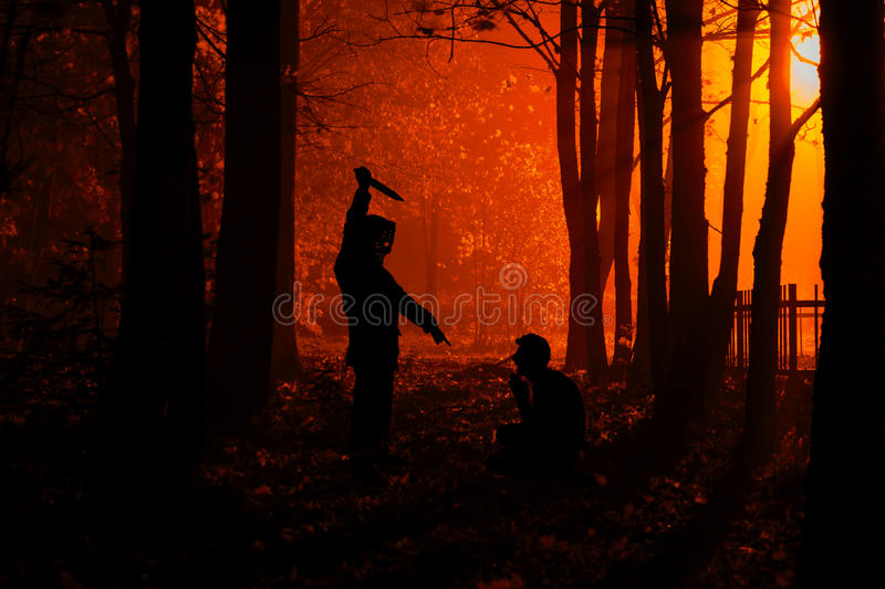 Murder in the park. Maniac kills his victim in the night deserted park. Silhouettes in night foggy forest stock photo
