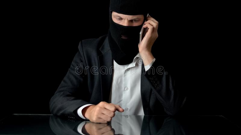 Murderer in mask talking on smartphone with crime partner, contract murder, gun stock image