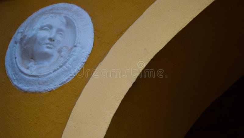 Mure curvas velhas da escultura do ornamento da arte da cara da casa da mulher da arcada do detalhe foto de stock