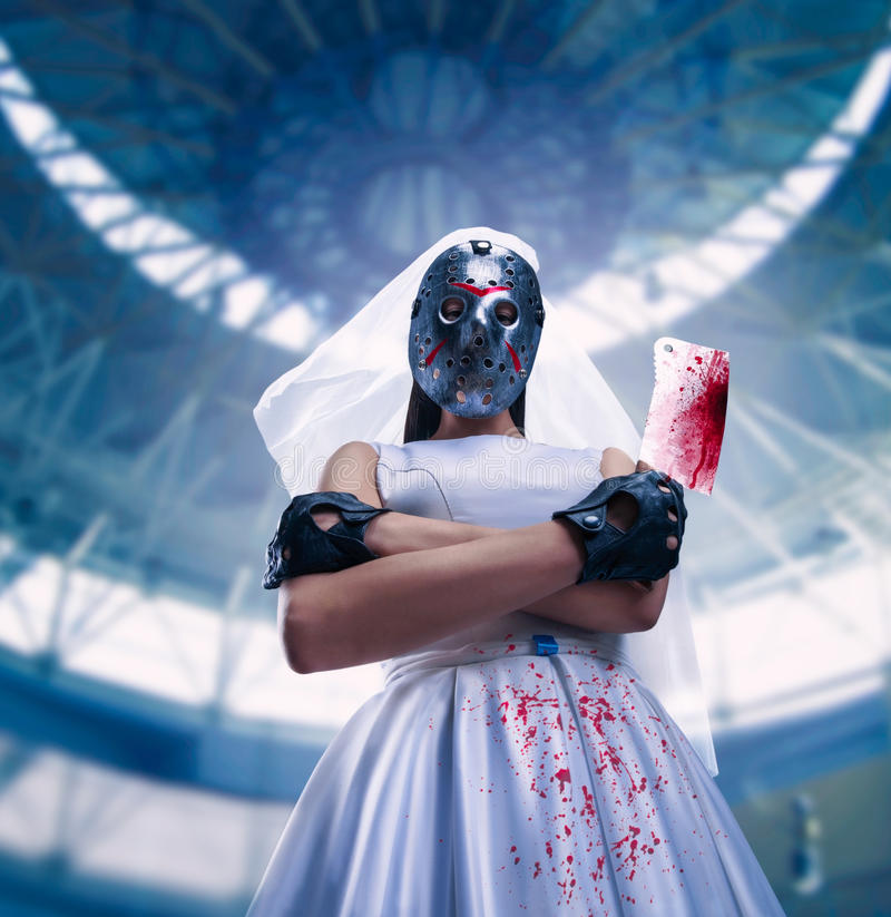 Murederer in wedding dress with meat cleaver. Serial murederer in wedding dress with bloody meat cleaver. Bride in hockey mask stock photo