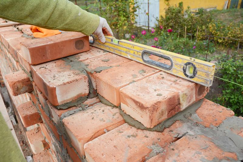 Mureri murverk Slut upp mureri på den husCnstruction platsen Murare Using en andenivå som kontrollerar nolla för tegelstenvägg royaltyfria bilder
