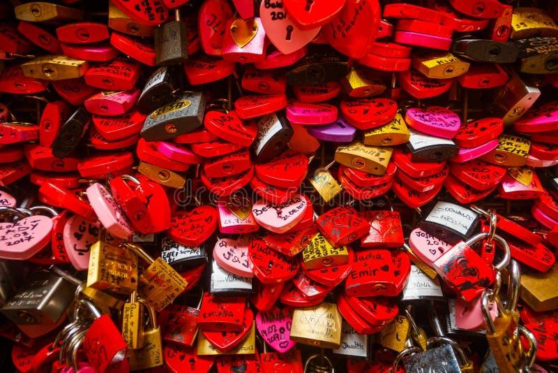 Murez complètement des serrures rouges et roses d'amour formées comme coeurs photos stock