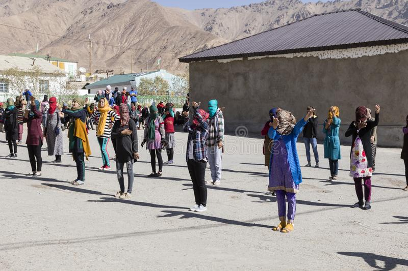 Murghab, Tajikistan, August 23 2018: Kyrgyz girls and young women are practicing a dance on the playground of a school in Murghab. Against the strong sunlight stock images