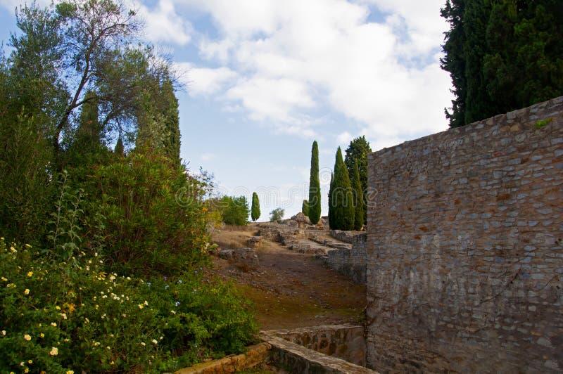Muri di pietra antichi, fiori, cespugli e alberi Nuvole bianche nel cielo azzurro Siviglia, Spagna fotografia stock libera da diritti