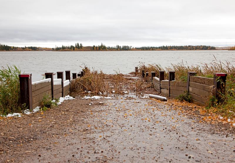Murky boat launch. A canoe or boat ramp leading to a marshy swamp in autumn royalty free stock image