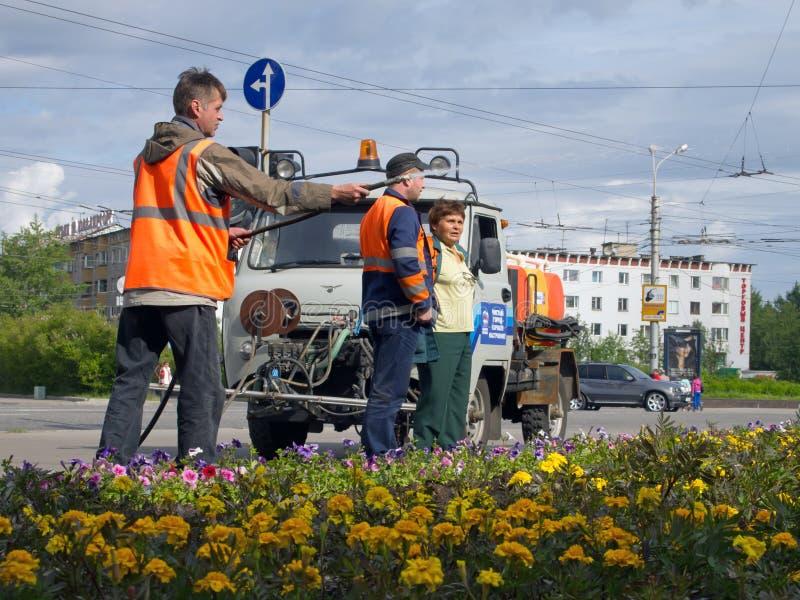 Murmansk, Rússia - 21 de junho de 2013, empregados das utilidades urbanas que molham o gramado no quadrado na cidade de Murmansk foto de stock royalty free