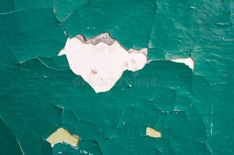 Muro de cemento agrietado pintado con la pintura verde abstraiga el fondo foto de archivo