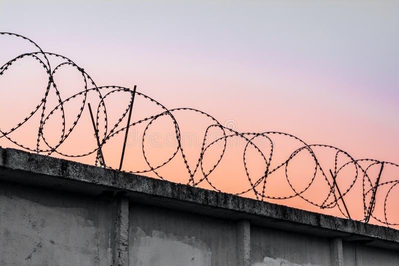 Muro de cemento con alambre de púas contra un cielo de igualación anaranjado azul fotografía de archivo