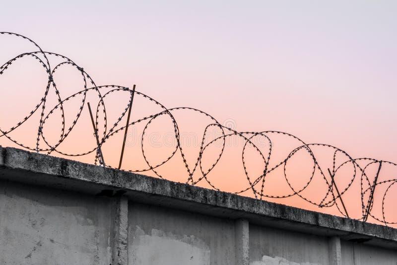 Muro de cemento con alambre de p?as contra un cielo de igualaci?n anaranjado azul imagen de archivo