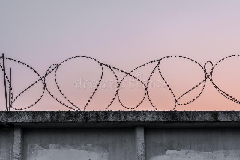 Muro de cemento con alambre de p?as contra un cielo de igualaci?n anaranjado azul foto de archivo