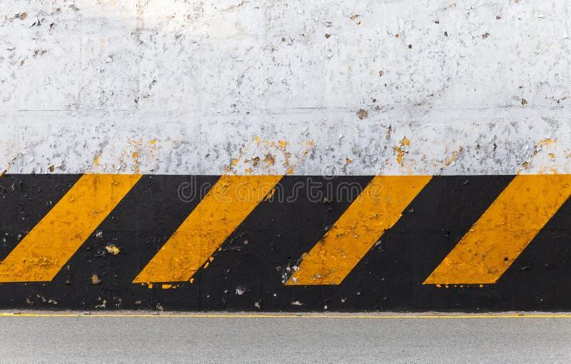 Muro de cemento con el modelo rayado de la precaución foto de archivo libre de regalías
