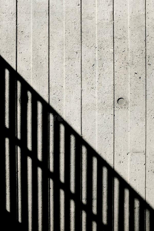 Muro de cemento con líneas verticales y una sombra imágenes de archivo libres de regalías