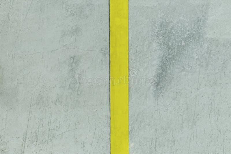Muro de cemento filmado en tiempo oscuro tiene una tira de color amarillo Dividido en dos porciones foto de archivo libre de regalías