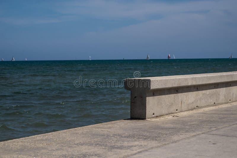Muro de cemento por el mar fotos de archivo