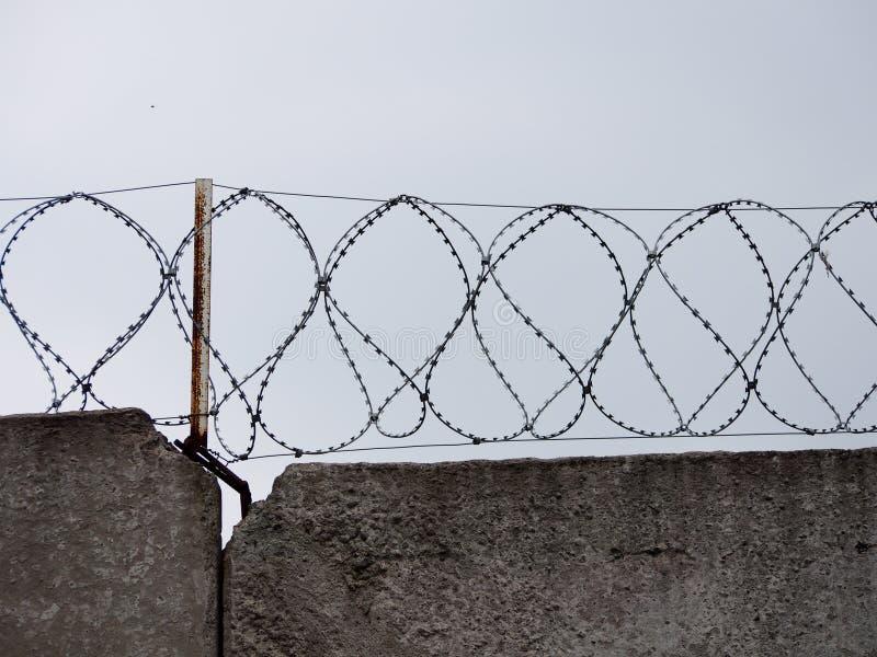 Muro de cimento com as bobinas do arame farpado foto de stock royalty free
