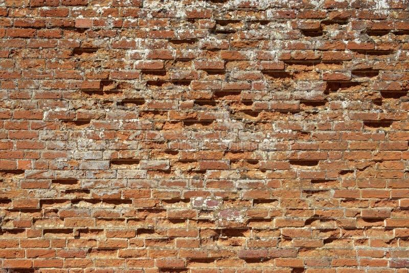 Muro de tijolos vermelhos muito velho, danificado, mal reparado imagem de stock