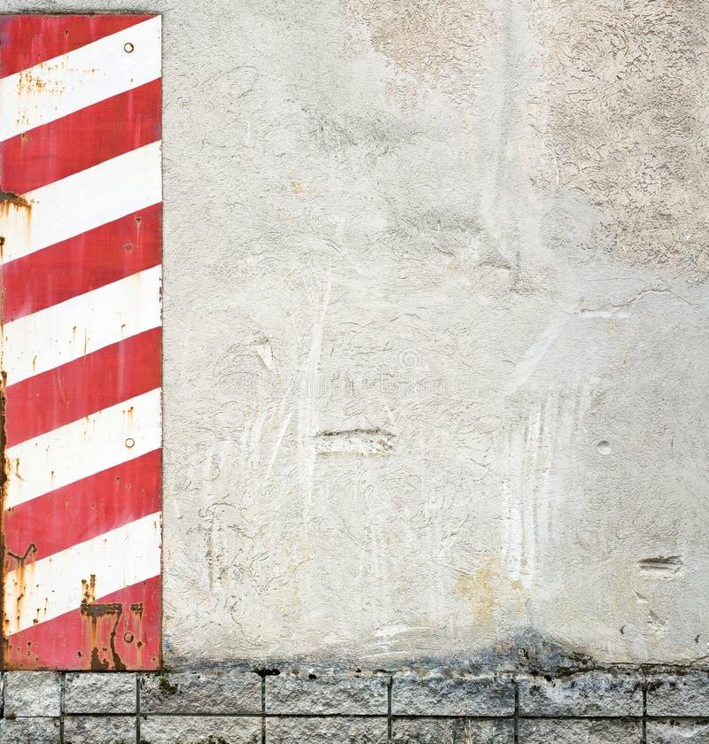 Muro di cemento con le bande d'avvertimento fotografia stock