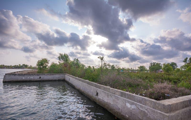 Muro di cemento costruito fra il lago Ashtamudi e l'isola di Munroe per l'inondazione di minimizzazione fotografia stock