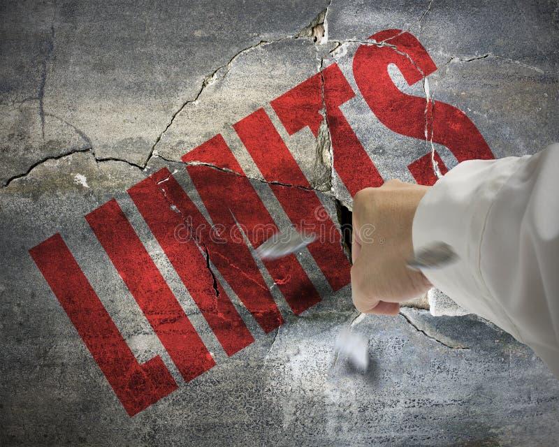 Muro di cemento di perforazione e incrinato con la parola LIMITI su e piccolo fotografie stock