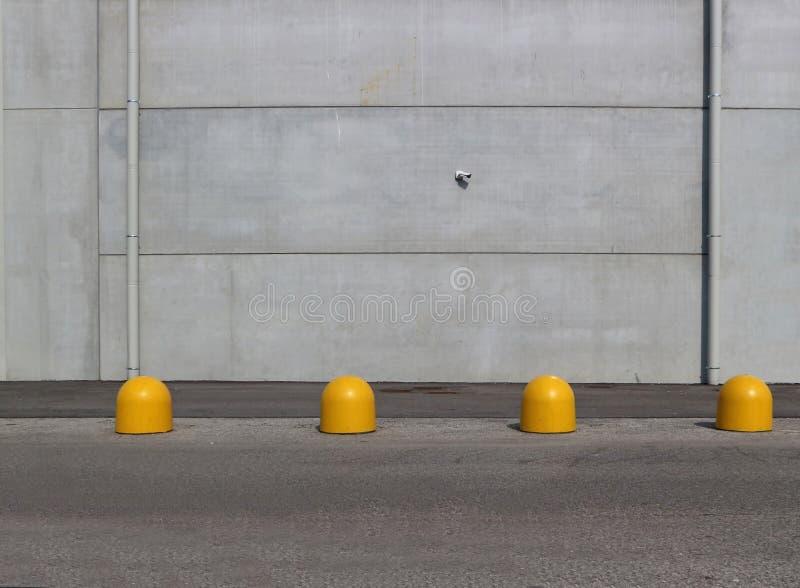Muro di cemento grigio con una strada asfaltata e le bitte gialle del cemento nella parte anteriore Fondo urbano per lo spazio de fotografia stock libera da diritti
