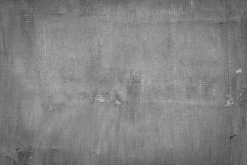 Muro di cemento grigio scuro incrinato con rete, i fori e le macchie fotografia stock libera da diritti