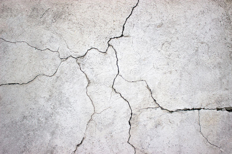 Muro di cemento incrinato coperto di struttura grigia del cemento come backgr fotografie stock libere da diritti
