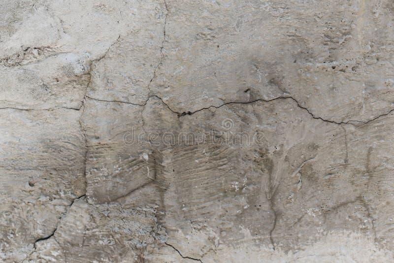 muro di cemento incrinato coperto di superficie grigia del gesso come fondo fotografia stock