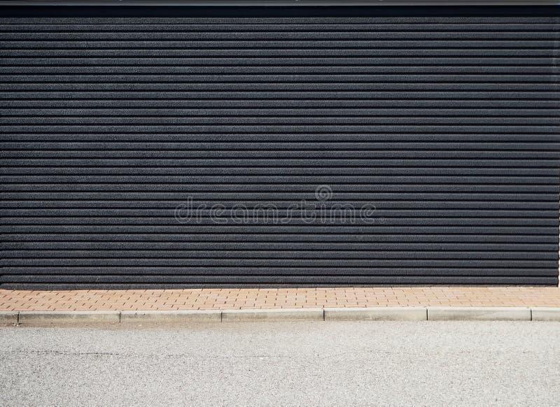 Muro di cemento nero con le bande orizzontali, un marciapiede marrone delle mattonelle e una strada asfaltata davanti  immagini stock