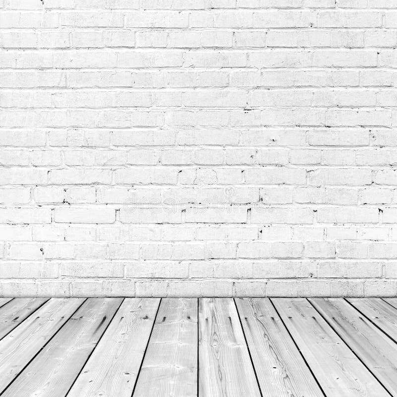 Muro di mattoni bianco e pavimento di legno, interno astratto fotografie stock