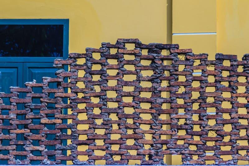 Muro di mattoni cellulare Grungy con la vecchia parete gialla d'annata e il blac immagine stock libera da diritti