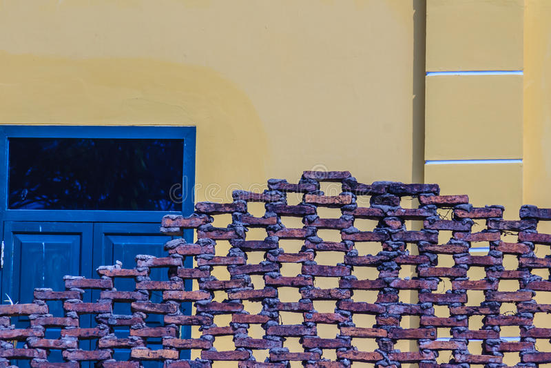Muro di mattoni cellulare Grungy con la vecchia parete gialla d'annata e il blac fotografie stock libere da diritti