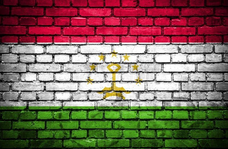 Muro di mattoni con la bandiera dipinta del Tagikistan illustrazione vettoriale