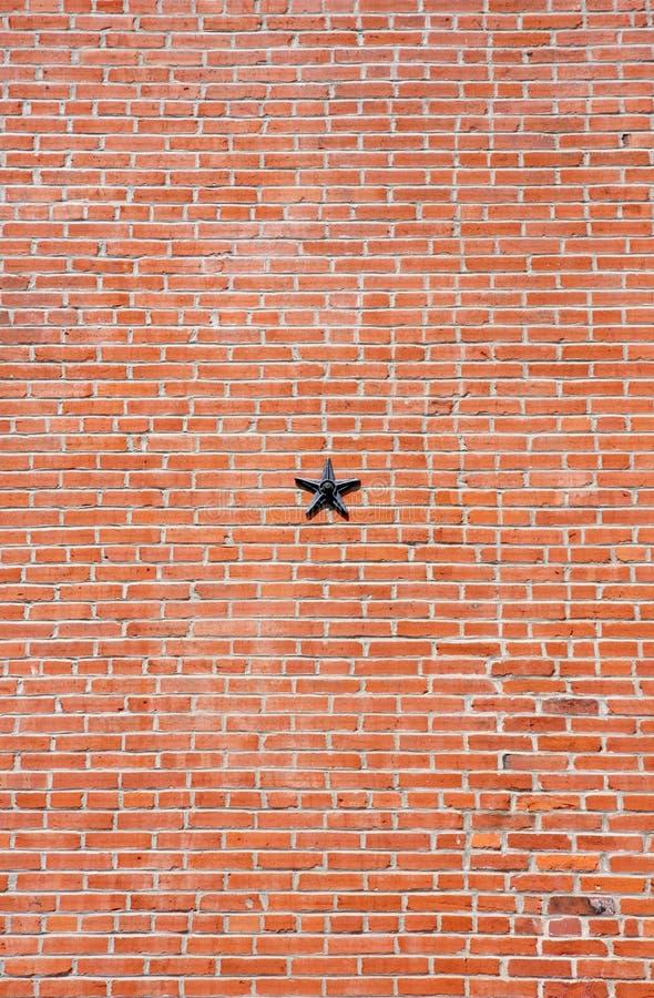 Muro di mattoni con la stella del metallo immagine stock libera da diritti