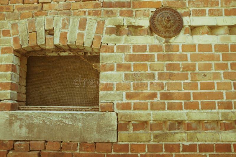 Muro di mattoni con la vecchia finestra del granaio immagine stock