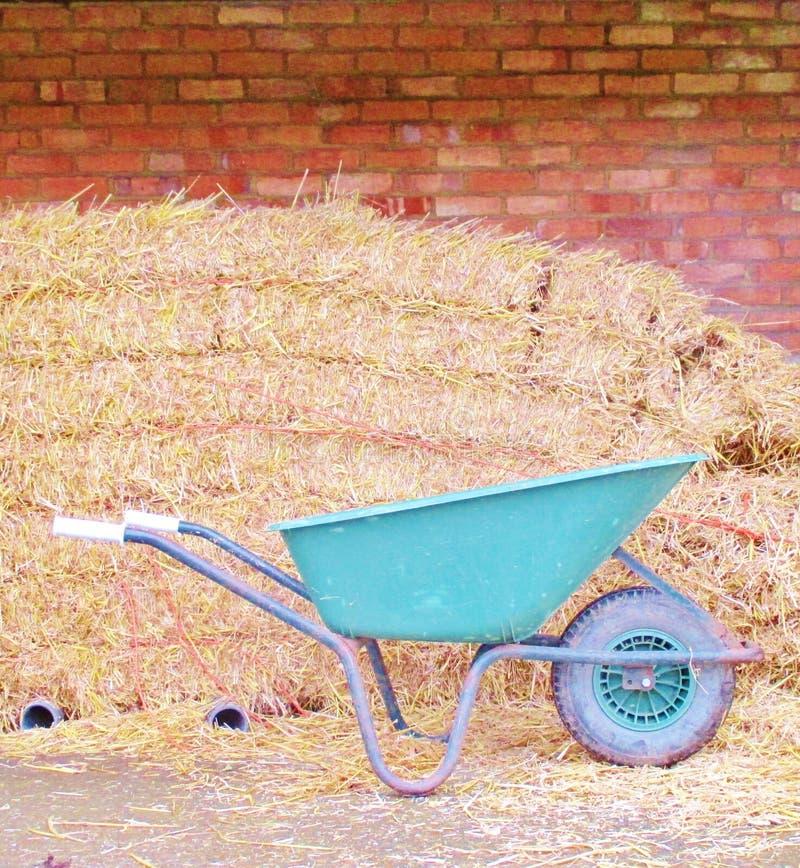 Muro di mattoni con le balle di fieno e la carriola di ruota fotografie stock libere da diritti