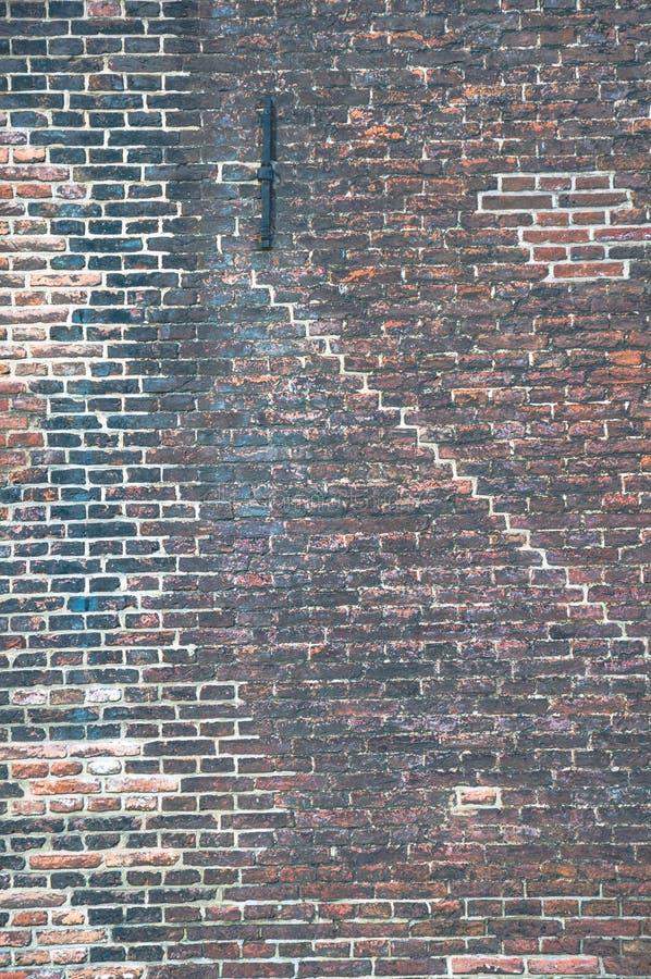 Muro di mattoni con molti strati di vecchia pittura e dei modelli differenti immagini stock