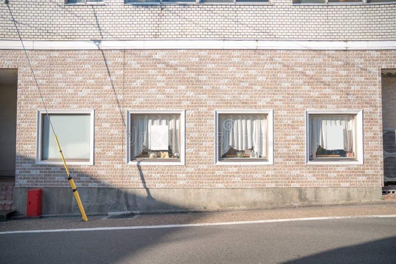 Muro di mattoni cremoso pastello con la finestra e la tenda nel Giappone fotografia stock libera da diritti